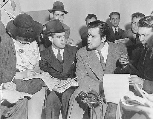 Photo of Orson Welles and reporters (Credit: Acme News Photos, via Wikimedia Commons)