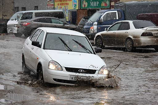 Photo of a car being caught by a flooded pothole